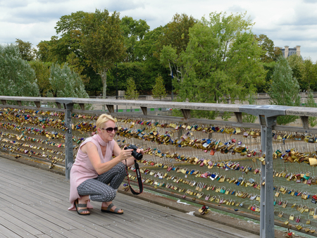 Paris, France - August 21, 2018: An unidentified woman take pictures of the padlocks on the bridge in Paris