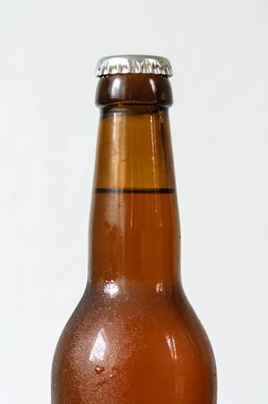 Cold beer bottle without label on wooden table back-lit isolated on white background Stock Photo