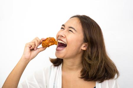 Feliz joven mujer asiática con pollo frito, ella sosteniendo pollo frito en la mano, fondo blanco aislado