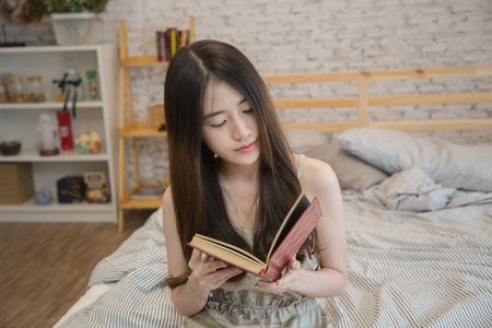 makeups: Young beautiful asian woman reading book on bed