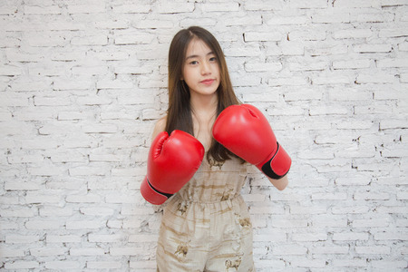 makeups: Young beautiful asian woman put on red boxing gloves, on White brick background
