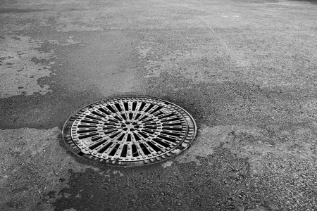 b w: Sewer hatch on the main road B W Stock Photo