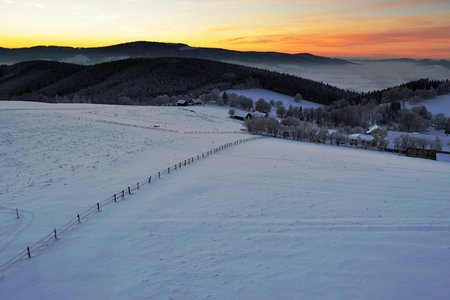 Winter sunset. Cold winter evening in the mountains. Last rays above horizont. photo
