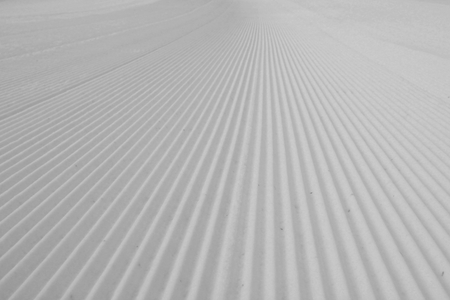 groomer: Snow groomer tracks on a ski piste.