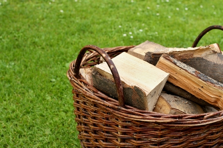 log basket: Basket with firewood in the garden. Firewood concept.