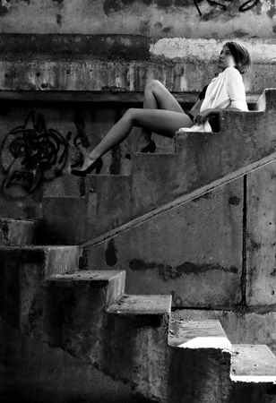 Urban sexy girl in building on ladder. Black and white concept.