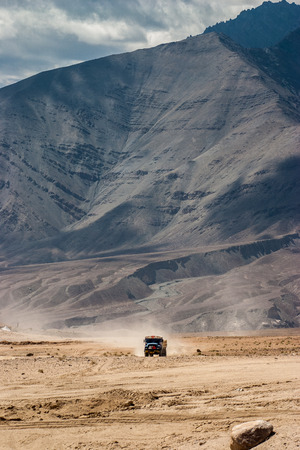 dropoff: Truck in the desert of Ladakh front of mountains Stock Photo