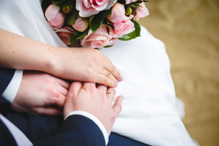 Gentle Hand of the Bridegroom in the Brides Hand Stock Photo