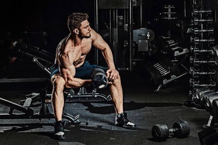 athletic man bodybuilder execute exercise with dumbbells for biceps and sitting in dark gym Stock Photo