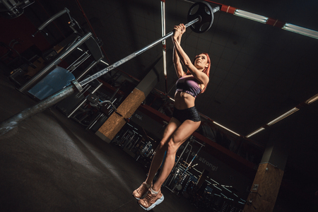 beautiful fitness sporty young girl holds a barbell arches her back