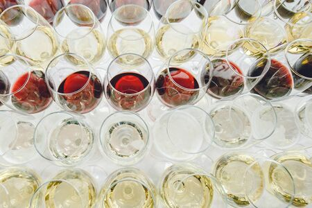 A lot of glasses of red and white champagne in a luxurious atmosphere view from above. Stylish photo of alcohol . Secular reception, new year, wedding. champagne glasses arranged lined in a long row Stock fotó