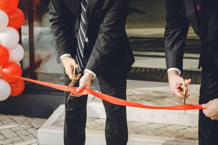 Businessman cutting red ribbon with pair of scissors. Two man in a classic black official suit cuts a red tape opening place Archivio Fotografico