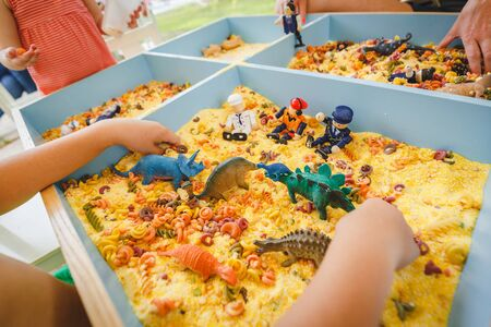 child plays with toys dinosaurs and little soldiers in an artificial yellow sandbox. Little green dinosaurs. kindergarten preschool.