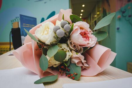 beautiful wedding bouquet with white and pink roses and other colorful flowers lying on the table close-up. Stock fotó