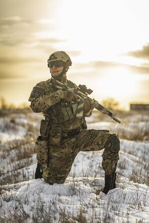 equipped army soldier Man in the winter khaki camouflage is patrolling or patrol field territory. commandos with full equipment helmet and gun watch battlefield. Modern army soldier