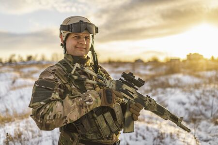 equipped army soldier Man in the winter khaki camouflage is patrolling or patrol field territory. commandos with full equipment helmet and gun watch battlefield. Modern army soldier. Reklamní fotografie
