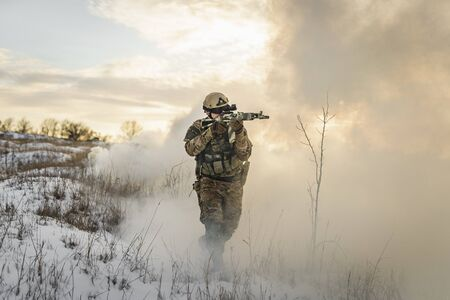 Soldier army man running through the smoke and explosions sun backlight and smoke background. modern warfare. atmosphere of battle. commandos on the winter battlefield in the smoke. Imagens
