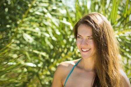 Girl smiling on the background of palm leaf Foto de archivo