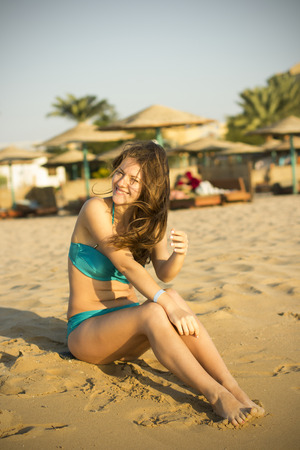 Wind develops the hair of a girl who is sitting on the beach