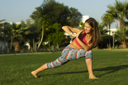 Girl doing yoga exercises on the lawn