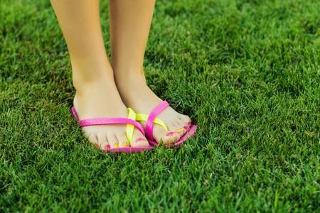 Women legs in sneakers standing on the lawn