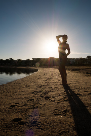 Sweet, slender girl stands on the beach against the sunset. Silhouette of a swimmer in a swimsuit. Foto de archivo