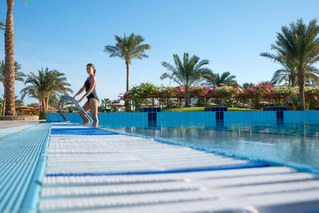 Young woman comes out of the sports pool in a beautiful piece-work swimsuit. Active rest of modern people at the resort.