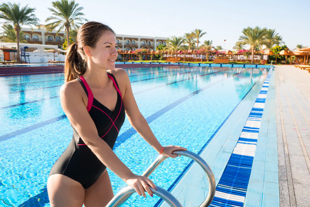 Young woman comes out of the sports pool in a beautiful piece-work swimsuit. The swimmer looks forward standing on a small staircase.