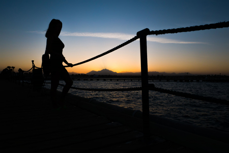 Silhouettes of a girl standing on a pier near the sea against the background of a sunset in the mountains.