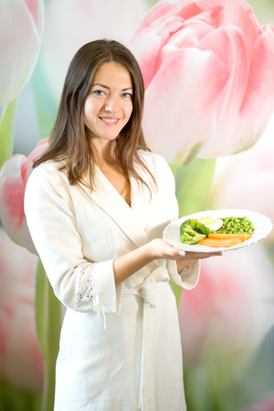 A young woman is holding a plate of boiled vegetables. Propaganda of proper nutrition.