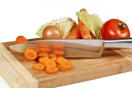 Vegetables and knife on cutting board isolated on white background