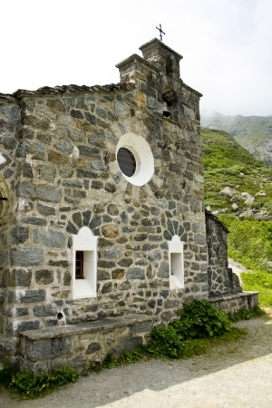 Little stone church with high mountains in background  Stock Photo