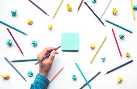 La main des hommes écrit sur du papier à lettres avec un crayon coloré sur fond blanc. La créativité d'entreprise et les concepts d'idées d'éducation Banque d'images