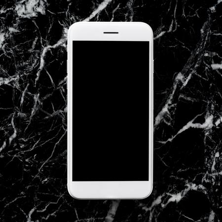 Blank smartphone on marble black stone table background Stok Fotoğraf