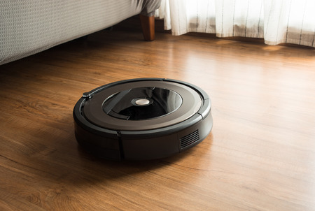 Robot vacuum cleaner on wood,laminate floor.Smart life concepts ideas 免版税图像