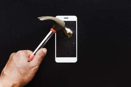 Main masculine avec un marteau sur un bouclier en verre trempé ou une couverture d'écran de film. Idées de concepts de protection de téléphone portable