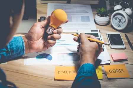 Businessman holding light bulb with worktable,ideas,motivation,innovation,creativity concepts