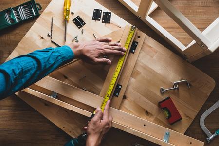 Mężczyzna składa drewniane meble, naprawia lub naprawia dom za pomocą żółtej taśmy mierniczej. Widok z góry