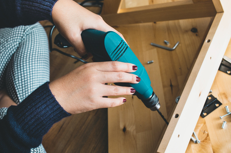 Woman assembly wooden furniture,fixing or repairing house with drill tool.modern living concepts ideas