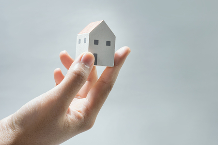 House model on human hands.Savings money,building construction,architecture,real estate and property concept