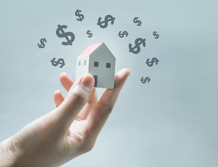 Modèle de maison sur les mains de l'homme avec l'icône dollar. Économies d'argent et concept immobilier Banque d'images