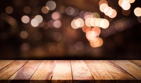 Holztischplatte mit unscharfem hellem Bokeh im dunklen Nachtcafé, Restauranthintergrund. Lifestyle- und Feierkonzepte