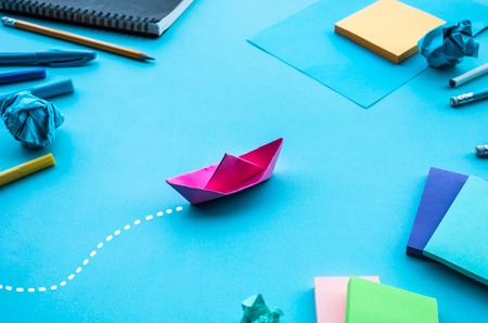 Business direction or goal concepts with boat paper on blue worktable background.investment success ideas.situation challenge