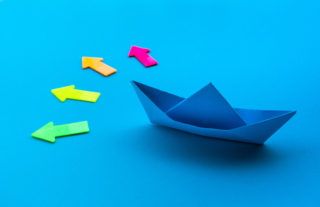 Business direction with boat paper and arrow on blue background.investment success concepts ideas.situation decided