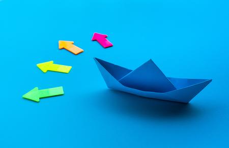 Direction de l'entreprise avec papier bateau et flèche sur fond bleu.idées de concepts de réussite d'investissement.situation décidée Banque d'images