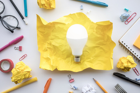 Inspiration creativity concepts with lightbulb in paper crumpled ball on worktable.Business ideas solution and human performance.Top view
