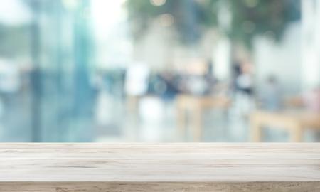 Mesa de madera sobre vidrio de ventana borrosa, fondo de pared con vista a la ciudad. Para exhibición de productos de montaje o diseño visual clave Foto de archivo