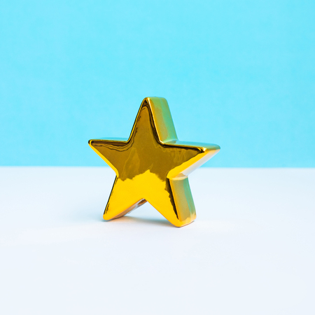 Gold star on pastel color background.Minimal style