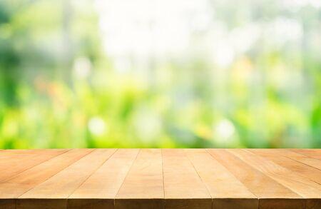 Leere Holztischplatte auf Unschärfe des frischen grünen abstrakten Hintergrunds. Für die Montage von Produktanzeigen oder das Design von Key Visual Layout