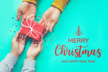 Merry christmas with male gives a gift to female with copy space background.happiness moment concepts ideas